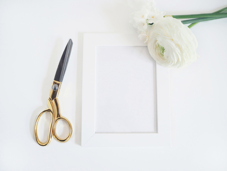 Styled stock photo. Feminine product mockup with bunch of buttercup, Ranunculus and daffodil flowers, blank white frame and golden scissors on white background. Flat lay, top view. Stok Fotoğraf