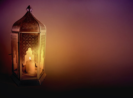 Ornamental Arabic lantern with burning candle glowing at night. Greeting card, invitation for Muslim community holy month Ramadan Kareem. Dark background with a lot of empty space.