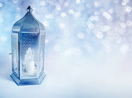 Ornamental Arabic lantern with burning candle glowing at night. Greeting card, invitation for Muslim community holy month Ramadan Kareem. Glittering festive blue background with bokeh lights. Фото со стока