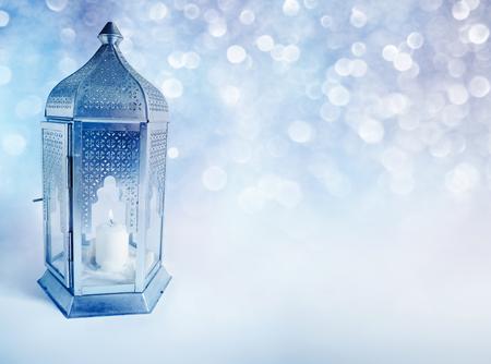 Sier Arabische lantaarn met brandende kaars gloeien 's nachts. Wenskaart, uitnodiging voor de heilige maand Ramadan Kareem voor de moslimsgemeenschap. Glanzende feestelijke blauwe achtergrond met bokeh lichten.