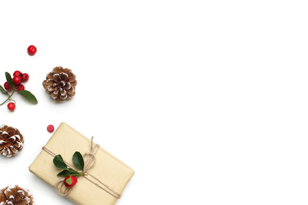 Christmas festive styled stock image composition. Handmade gift box, red berries and pine cones isolated on white wooden background. Flat lay, top view. Stock Photo