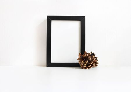 Black vertical blank wooden frame mockup with pine cones lying on the white table. Poster product design. Styled stock feminine photography. Home decor. Christmas winter concept.