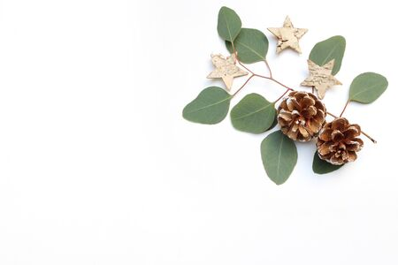 Christmas festive styled stock image. Floral frame composition with pine cones, eucalyptus branches and birch wooden stars on white wooden background. Flat lay, top view. Empty copy space.