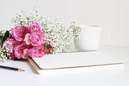 Bruiloft gestileerde voorraadfoto. Stilleven met roze rozen, baby's ademen Gypsophila-bloemen, witte kop, potlood en notitieboekje. Bloemensamenstelling. Afbeelding voor blog of sociale media.