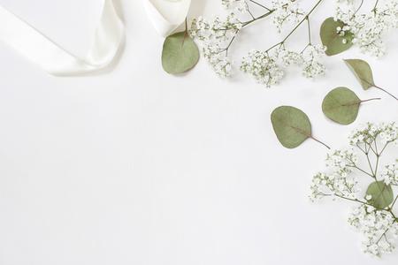 Stylizowane zdjęcie stockowe. Kobiecy ślubny makieta pulpitu z babys oddech kwiaty łyszczec, suche zielone liście eukaliptusa, satynowa wstążka i białe tło. Pusta przestrzeń. Widok z góry. Zdjęcie na bloga.