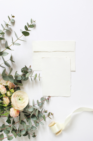 Feminine wedding, birthday desktop mock-ups. Blank craft paper greeting card, envelope. Eucalyptus branches, pink roses and Persian buttercup flowers. White table background. Flat lay, top view. Archivio Fotografico - 95632757