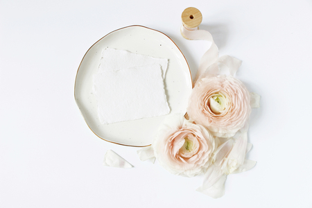 Feminine wedding, birthday desktop mock-up scene. Porcelain plate, blank craft paper greeting cards, silk ribbon, blush pink Persian buttercup flowers. White table background. Flat lay, top view.
