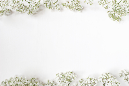 Styled stock photo. Feminine wedding desktop with babys breath Gypsophila flowers on white background. Empty space. Floral frame, web banner. Top view. Picture for blog or social media. Stock Photo