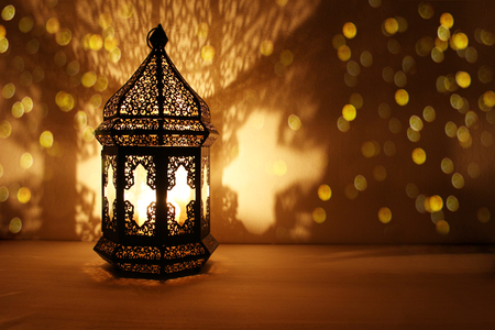 Ornamental Arabic lantern with burning candle glowing at night and glittering golden bokeh lights. Festive greeting card, invitation for Muslim holy month Ramadan Kareem. Dark background. Фото со стока