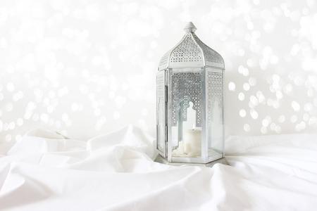 Lanterna ornamentale marocchina in argento, araba su plaid in lino bianco. Candela accesa, scintillanti luci bokeh. Biglietto di auguri per il mese santo della comunità musulmana Ramadan Kareem. Sfondo festivo.