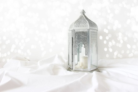 Ornamental silver Moroccan, Arabic lantern on white linen throw. Burning candle, glittering bokeh lights. Greeting card for Muslim community holy month Ramadan Kareem. Festive background.
