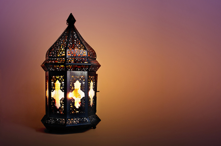Ornamental dark Moroccan, Arabic lantern on the table. Burning candle in the night. Greeting card for Muslim community holy month Ramadan Kareem. Festive blurred background.