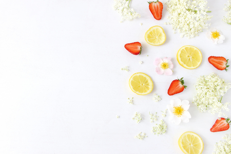 Styled stock photo. Spring or summer fruit composition. Sliced lemons, elderflowers, strawberries and wild roses isolated on white wooden table background. Food pattern. Flat lay, top view. Stock Photo