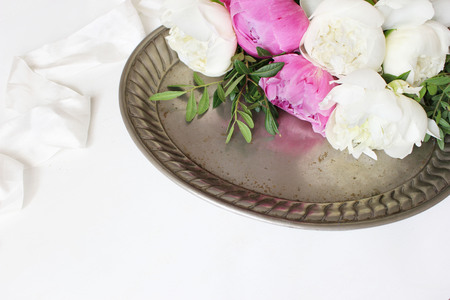 Styled stock photo. Feminine wedding or birthday table composition with floral bouquet. White and pink peonies flowers on old vintage silver tray and silk ribbon. White background. Picture for blog.