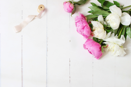 Styled stock photo. Feminine wedding or birthday table composition with floral bouquet. White and pink peonies flowers and spool of silk ribbon. White wooden background. Flat lay, top view.