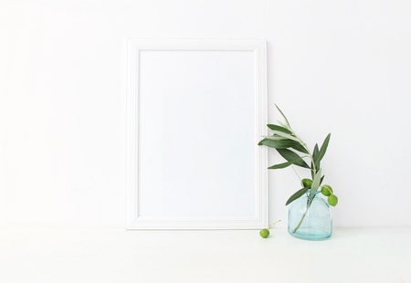 White vertical blank wooden frame mockup with a green olive branches in blue glass vase lying on the table. Mediterranean summer poster product design. Styled stock feminine photography. Home decor.