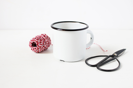 Winter still life composition with blank white metal coffee mug, vitage scissors and red decorative gift rope on white table background. Christmas styled stock photo, rustic scene. Product mockup. Stock Photo