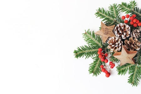 Christmas festive styled floral composition. Pine cones, fir tree branches, red rowan berries and wooden stars on white table background. Decorative frame, web banner. Flat lay, top view. Copy space. Banco de Imagens