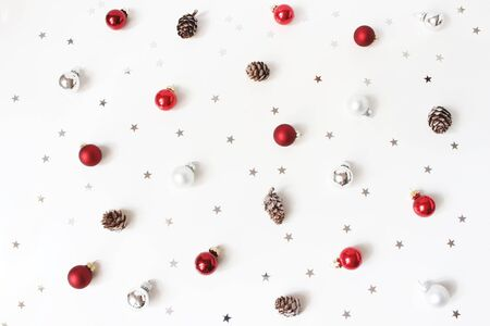 Christmas styled composition. Red Christmas glass balls, baubles, silver confetti stars and larch cones on white table background. Flat lay, top view. Decorative winter pattern