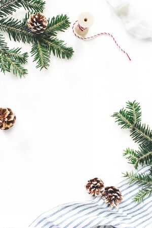 Christmas festive composition. Decorative floral frame. Fir tree branches border. Pine cones, gift rope, ribbon and linen cloth on white table background. Flat lay, top view. Copy space, vertical.