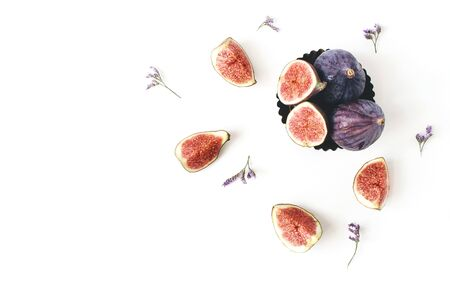 Fresh ripe purple figs composition. Food Photo. Sliced and whole exotic fruit in vintage bowl. Limonium flowers on a white table background. Floral pattern, decorative corner. Flat lay, top view.