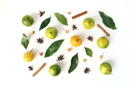 Christmas styled stock composition. Tangerine citrus fruit and leaves, cinnamon sticks, anise stars and little apples on white table background. Christmas, winter holiday concept. Flat lay, top view.