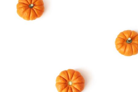 Autumn frame made of little orange pumpkins isolated on white table background. Fall, Halloween and Thanksgiving concept. Styled stock flat lay photography. Top view. Empty space for text. Vegetable.