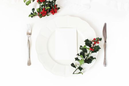 Traditional Christmas table place setting. Silver cutlery, holly berry branches, porcelain plate and silk ribbon. Blank card mockup. Winter wedding or restaurant menu concept. Flat lay, top view.