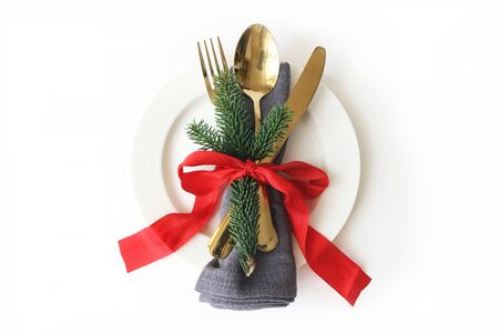 Traditional Christmas table place setting. Golden cutlery, linen napkin, green spruce branches, plate and red ribbon decoration isolated on white background. Holidays background. Flat lay, top view