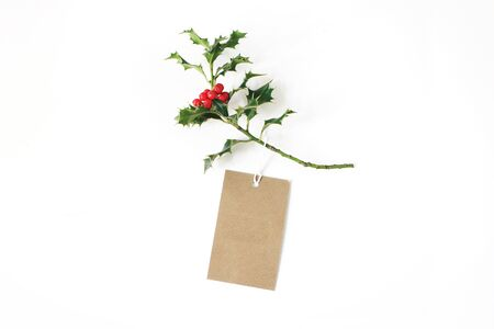 Close-up of craft paper gift tag with rope and green holly branch with red berries isolated on white table background. Christmas composition, top view. Banco de Imagens