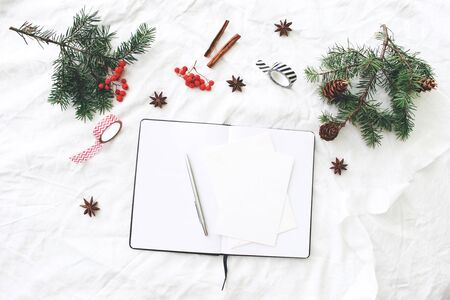 Christmas composition. Blank note pad, greeting cards mock-up scene. Christmas tree branches, red rowan berries, pine cones, washi tapes and cinnamon. White linen tablecloth background. Flat lay, top.