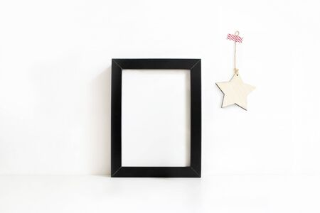 Vertical black blank wooden frame mockup on white table. Wooden star decoration hanging on the wall. Styled stock feminine photography. Home decor. Christmas winter concept.