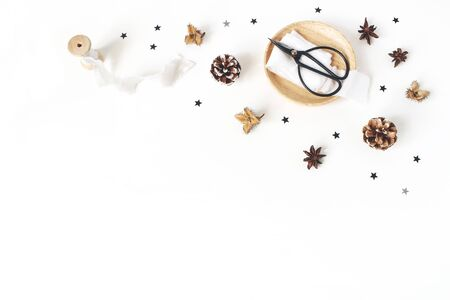Christmas craft composition. Decorative corner. Pine cones, silk and ribbons on white table background. Winter wedding. Flat lay, top view. Banco de Imagens