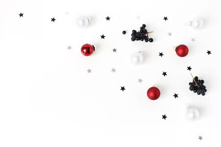 Christmas composition. Red and white Christmas glass balls, baubles, silver confetti stars and black privet, Ligustrum berries on white table background. Flat lay, top view. Decorative winter pattern.