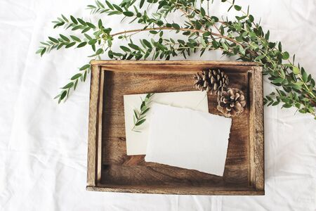 Christmas or winter wedding mock-up scene. Blank cotton paper greeting cards, old wooden tray, pine cones and green Eucalyptus parvifolia branch.White bed linen background. Flat lay, top view. Banco de Imagens