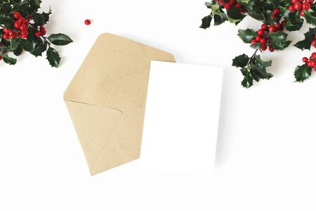 Christmas composition. Blank greeting card, envelope mock-up scene. Decorative banner. Holly berries and leaves berries on white table background. Flat lay, top view.
