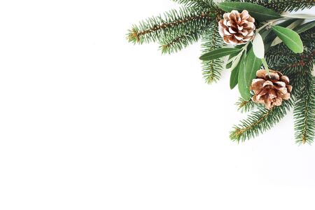 Christmas festive styled stock composition. Decorative corner. Pine cones, Fir and olive tree leaves and branches white wooden background. Flat lay, top view. Copy space.