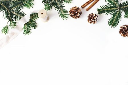 Christmas festive styled stock composition. Fir tree branches border. Pine cones, cinnamon and silk ribbon on white wooden background. Flat lay, top view. Copy space. Decorative floral web banner.