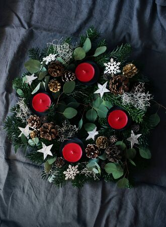 Christmas composition of advent wreath on dark grey table linen background. Made of evergreen fir tree branches, eucalyptus leaves, snowflakes, golden and natural pine cones. Flat lay, top view.