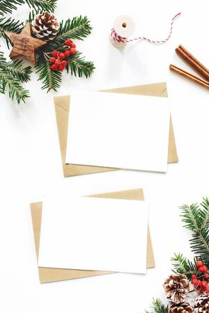 Christmas composition. Blank greeting card, envelope mock-up scene. Pine cones, fir tree branches, red rowan berries and wooden stars on white table background. Flat lay, top view, vertical.