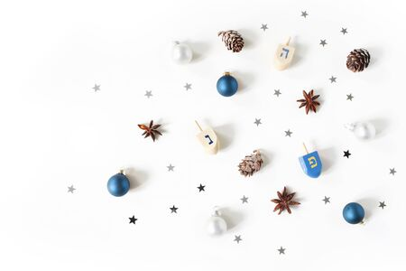 Hanukkah styled stock composition. Decorative pattern. Wooden dreidel toys, larch cones, anise and silver confetti stars decoration on white background. Flat lay, top view. Jewish design. Stock Photo