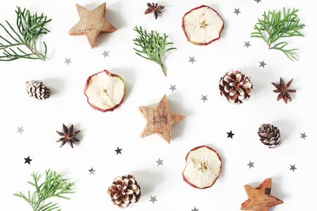 Christmas festive styled composition. Decorative pattern. Pine cones, dried apple fruit, cypress branches, anise, confetti and wooden stars isolated on white wooden background. Flat lay, top view Banco de Imagens