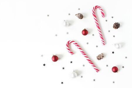 Christmas styled composition. Christmas red and white balls, baubles, candy canes, glittering silver stars confetti decoration and larch cones on white background. Flat lay, top view. Winter patttern.