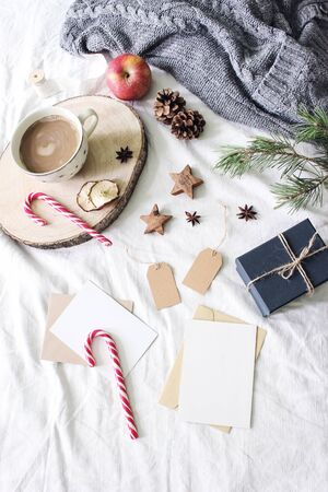 Christmas bed still life composition. Greeting cards, gift tags mockup scene. Cup of coffee, candy canes, gift box and wooden stars. White linen bed sheet background. Winter flat lay, top view. Banco de Imagens