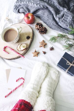 Christmas bed still life. Female legs in checkered pyjamas and woolen socks. Cup of coffee, candy canes and gift box. White linen bed sheet background with sweater. Winter flatlay, top view.