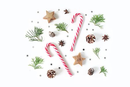 Christmas composition. Decorative winter pattern, banner made of cypress branches, pine cones, candy canes, anise, wooden and silver confetti stars. White table background. Flat lay, top view. Banco de Imagens