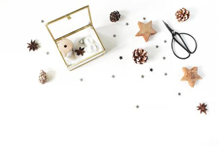 Christmas craft composition. Silk ribbons and Christmas balls in golden glass box. Vintage scissors, pine cones, silver confetti and wooden stars. White table background. Flat lay, top view Banco de Imagens