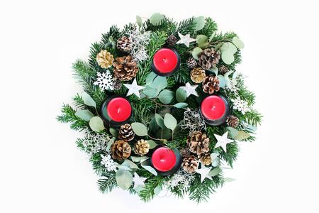 Christmas advent wreath isolated on white table background. Decorated by evergreen fir tree branches, eucalyptus leaves, snowflakes, golden and natural pine cones and red candles. Flat lay, top view.