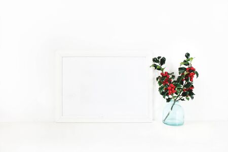 Horizontal white blank wooden frame mockup. Holly berry branches in blue glass vase on white table. Styled stock feminine photography. Home decor. Christmas winter concept.