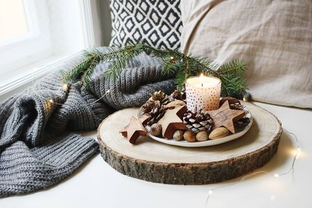 Winter festive still life scene. Burning candle decorated by wooden stars, hazelnuts and pine cones standing near window on wooden cut board. Glittering Christmas lights. Fir branch on wool plaid.